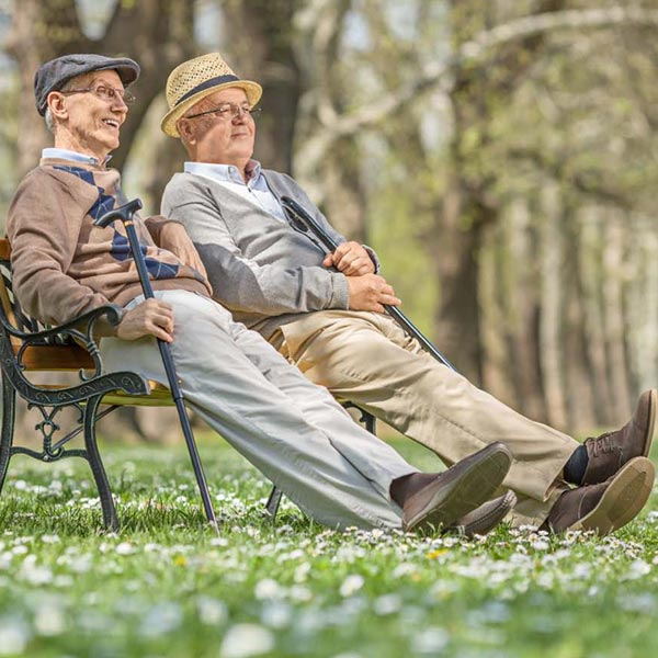2 older men sitting on bench in park