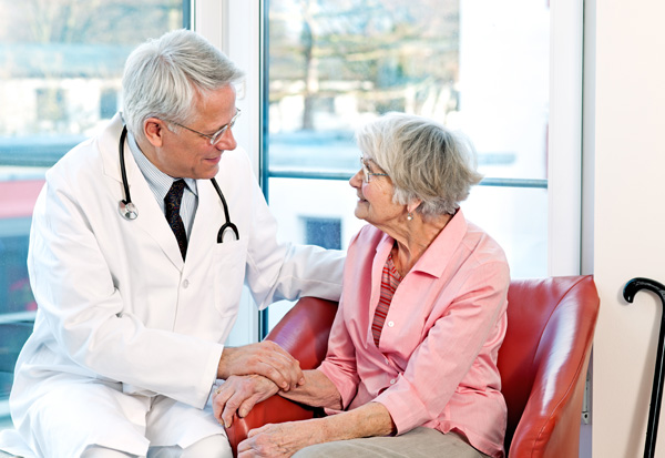Friendly doctor reassuring an elderly woman.