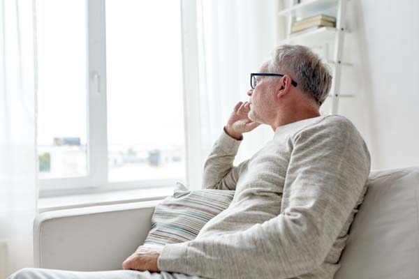 senior man in glasses thinking at home