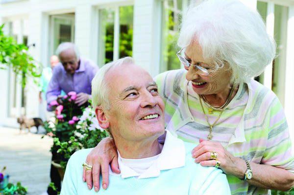 Senior couple smiling outdoors.