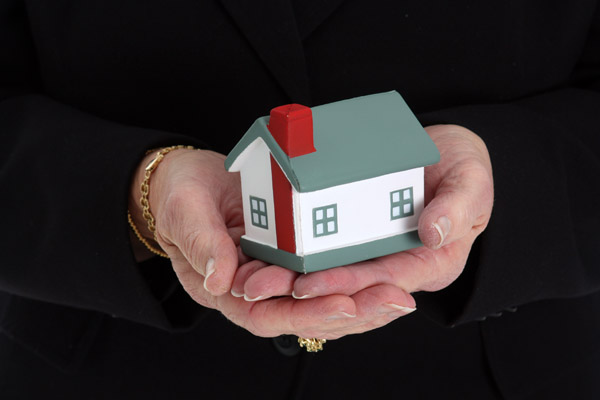 Senior woman holding a small house in her hands