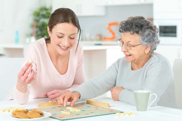 Grandmother and granddaughter playing a board game.