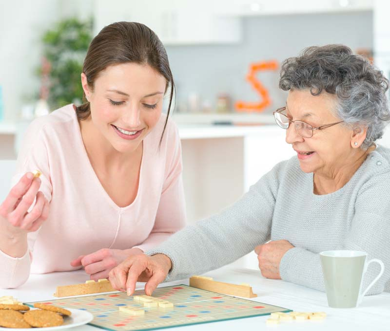 A senior women and home care aid enjoying playing a board game.