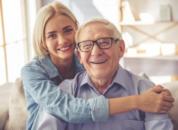 Photo of a senior man and his daughter enjoying one another's company.