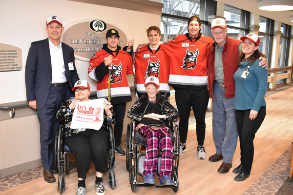 Players from the Adirondack Thunder hockey team visit seniors at The Wesley Community in Saratoga Springs, NY on Tuesday, January 15. Adirondack Thunder players (pictured in the middle from left to right) Dylan Walchuk, Will Smith and Dillon Kelley spent the afternoon engaging with seniors and staff at the Wesley Health Care Center.