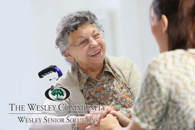 Elderly woman sharing good time with a home care aid.