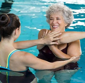 Aquatics Instructor working with Elderly Woman in Pool