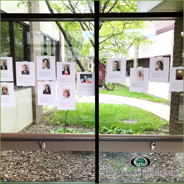 Photos of Wesley staff attached to a window.