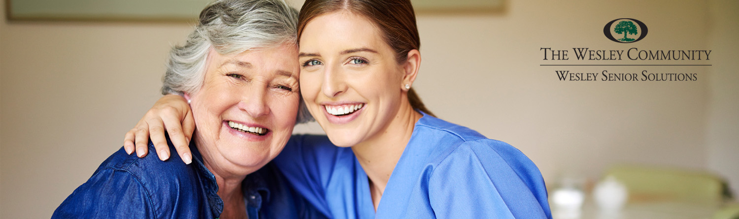 Home Care Aide and caregiver and female client smiling and looking at the camera.