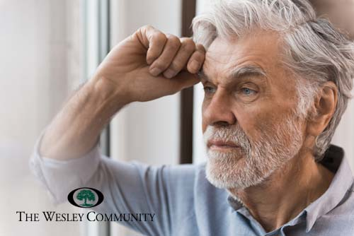 Senior man looking out a window with stress in his eyes.