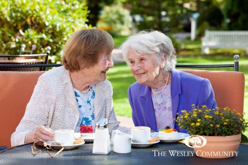 Two Happy Senior Women Sitting and Chatting at the Outdoor Table with Coffee and Snacks.