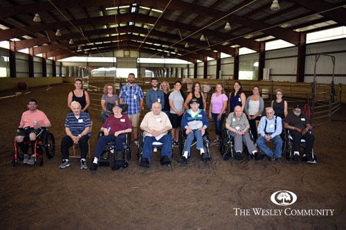 A multigenerational group posing in a large barn.
