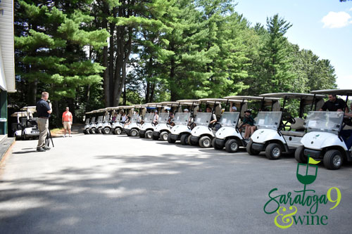 A man addressing a group in golf carts.
