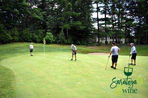 Four men on the greens playing golf.