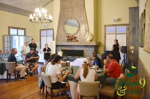 A woman addressing a group inside a golf clubhouse.