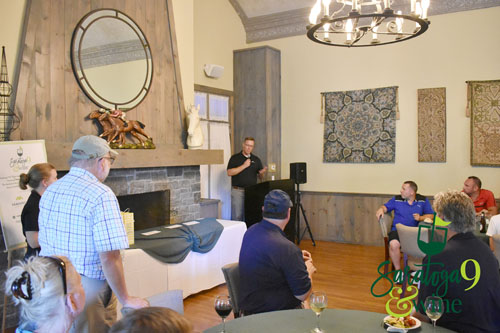 A man addressing a group of people inside a golf clubhouse.