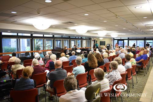 A large audience of seniors watching a classical music ensemble.