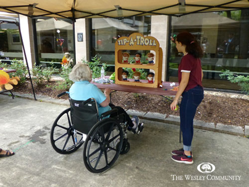 Senior in wheelchair playing Tip a Troll game