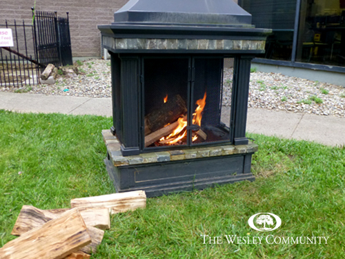 an outdoor fireplace lit with fire