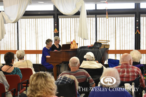 two seniors playing a duet on piano