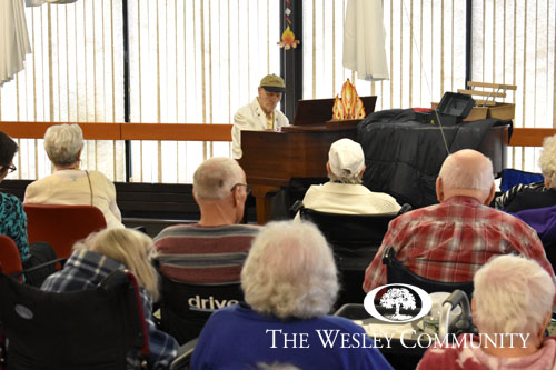 man playing piano for group of seniors