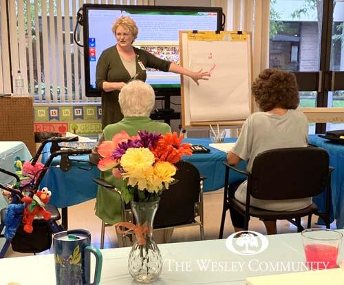 A woman instructing a senior arts class.