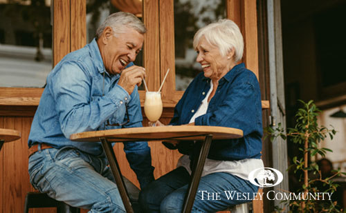 Cheerful senior couple sitting at cafe having a coffee. Senior man and woman sitting at restaurant table talking with cold coffee on table.