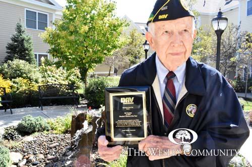 A WWII Veteran posing with an award in a garden.