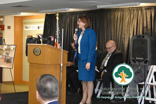 The Campaign for Springs Launch. A woman in a skirt and blazer at a podium and presenting the Campaign for Springs logo on a large screen. THere is a panel of people behind her and an audience in front of her.