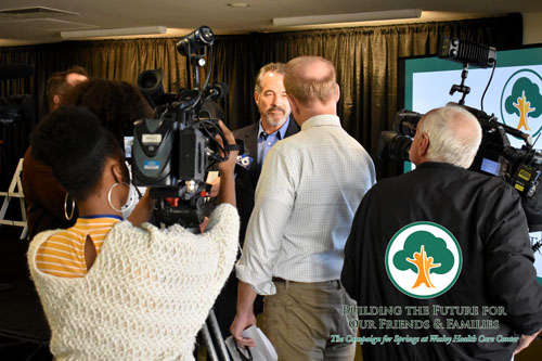 Campaign for Springs Launch. THis photo features a man in a blue shirt and blazer being interviewed by multiple news outlets. There are two people in the foreground with cameras and a man asking questions.