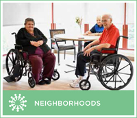 "A photo of two residents in wheel chairs enjoying a gathering area known as a ""neighborhood."""