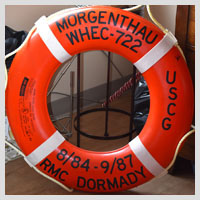 A photo of a orange life preserver, which is one of the decorations in Steve's room. It includes the dates that Steve served in The U.S. Coast Guard.