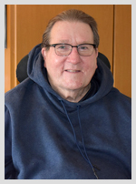 "A photo of a gentleman in a blue hooded sweatshirt. He is a resident of Wesley Health Care Center who is named ""Steve""."