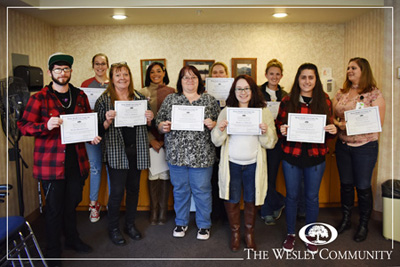 A group of people who graduated from Wesley's CNA Training Class. THey are smiling for the camera and displaying their diplomas.