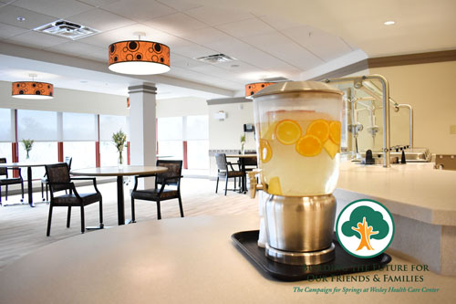 The renovated dining room on 5 Springs - A water dispenser with fresh fruit in it is displayed in the foreground. Behind it is a modern dining space with a wall of windows in the back and contemporary design details.