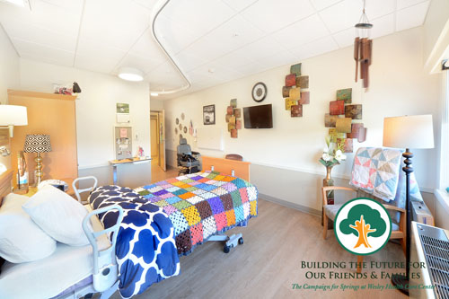 A resident's room on the nearlt renovated 5th floor of the Springs Building. THere is a brightly colored quilt on the bed, personal items on the walls and shelves and a modern lift system, which can transport the resident from their bed to the private bathroom.