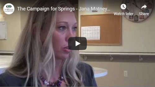A blond woman in formal wear being interviewed. There is a clock and a corkboard on the wall in the background. THis interview is for The Campaign for Springs.