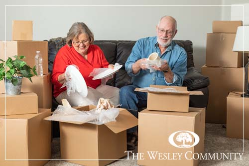 Senior adult couple sitting on a couch, smiling  and packing moving boxes.