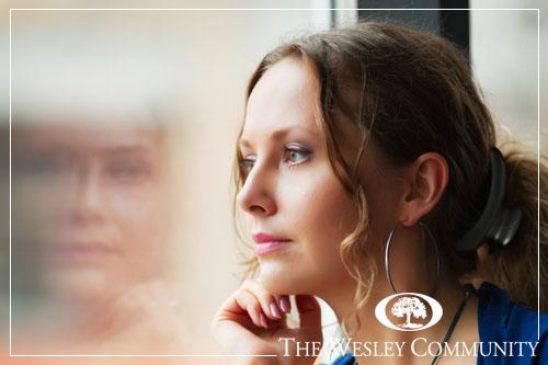 Beautiful young woman looking through a window.