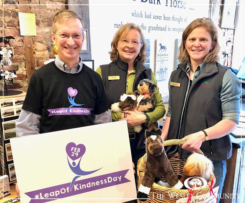 Two women and a man holding stuffed animals and smiling for the camera.