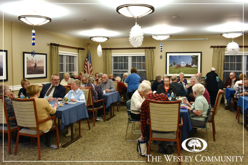 Residents and family sitting in a multi-table dining room.