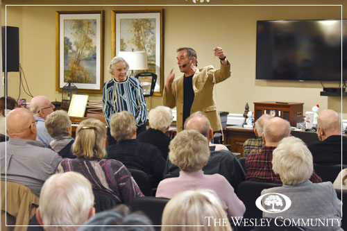 A magician with a volunteer entertaining a crowd of seniors and their families.