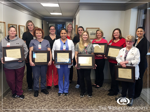 A group of nurses holding awards and smiling for the camera in a hallway.