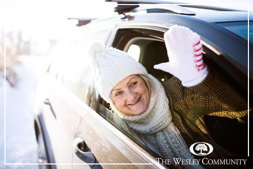 Senior woman in winter clothes waving from car