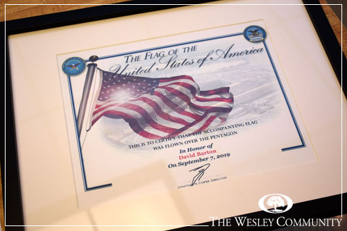 A plaque featuring the U.S. flag and a brown frame.