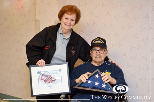 A woman presenting a veteran in a wheelchair with a flag and plaque.