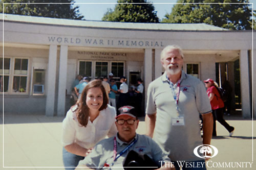 A woman and two men, one in a wheel chair, posing for a photo in front of the World War 2 Monument in Washington DC.