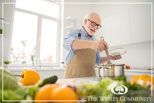 A senior man cooking in the kitchen with a big window behind him and ingredients in the foreground..