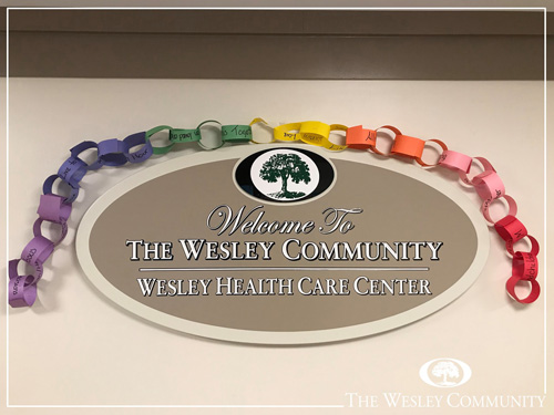 A sign for The Wesley Health Care Center decorated with rainbows.