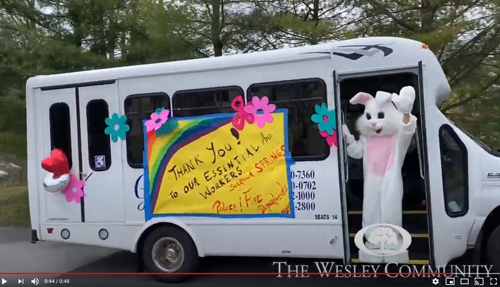 AN easter bunny waving from a bus in a parade.